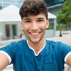 Closeup shot of handsome young man take a selfie in the city center. Guy is photographing self outdoor. Shallow depth of field with focus on smiling young man taking selfie.